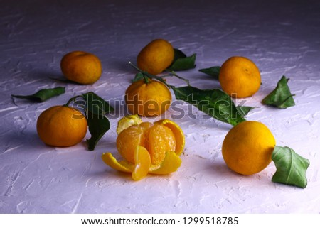 Tangerines. Natural tangerines with green leaves on the white textured background. Slice of a peeled tangerine. #1299518785