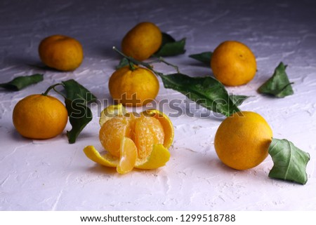 Tangerines. Natural tangerines with green leaves on the white textured background. Slice of a peeled tangerine. #1299518788