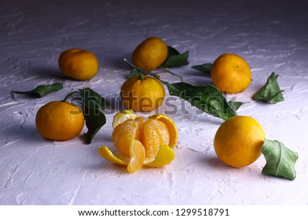 Tangerines. Natural tangerines with green leaves on the white textured background. Slice of a peeled tangerine. #1299518791