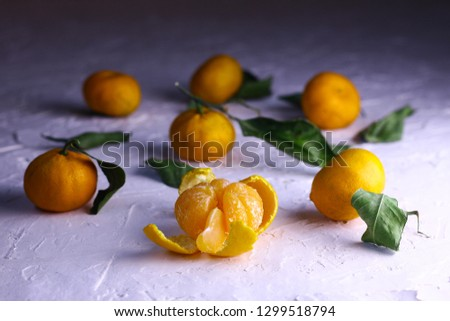 Tangerines. Natural tangerines with green leaves on the white textured background. Slice of a peeled tangerine. #1299518794