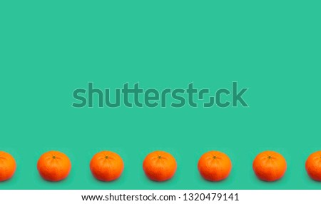 Tangerines on a green background, tangerines in a row #1320479141