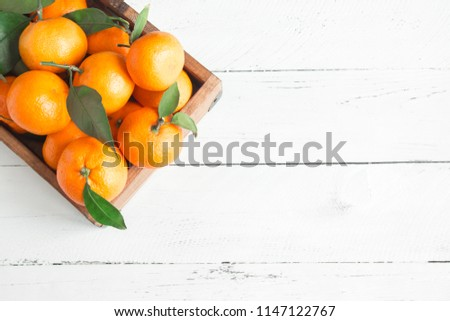Tangerines (oranges, clementines, citrus fruits) with green leaves over white wooden background with copy space #1147122767