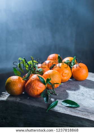 Tangerines oranges, mandarins, clementines, citrus fruits with leaves in basket over rustic wooden background, copy space #1237818868
