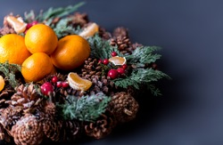 Tangerines with christmas decoration on dark wooden background. Tangerines with spruce. Christmas decoration
