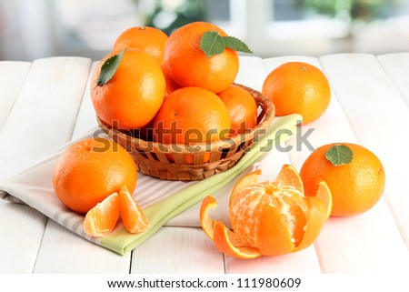 tangerines with leaves in a beautiful basket, on white wooden table