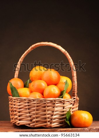 tangerines with leaves in a beautiful basket on wooden table on brown background