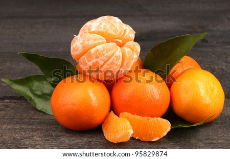 tangerines with leaves on wooden grey table