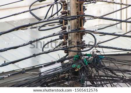 tangle of cables and wires on electric pole in the city. #1505612576