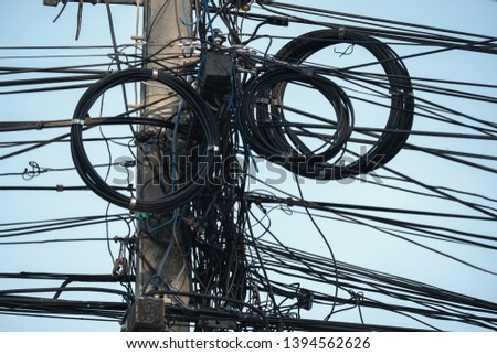 Tangled Electric Wire on the Post, Messy Danger Disorganized Wiring System. #1394562626