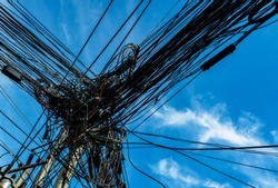 Tangled electrical wires on urban electric pole. Disorganized and messy to organization management concept. Tangled electrical wires should take underground wire for beautiful landscape.
