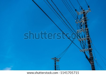 Tangled Electricity Wires and electricity pole, Power Utilities with Pole and Blue sky backdrop in Thailand #1141705715