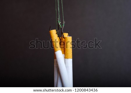 tangled strands with hooks on which hang the cigarettes, don't get caught on the hook of nicotine, black background #1200843436