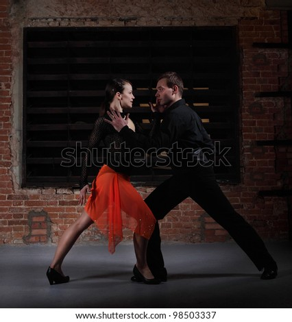 Tango dancers in action against brick wall