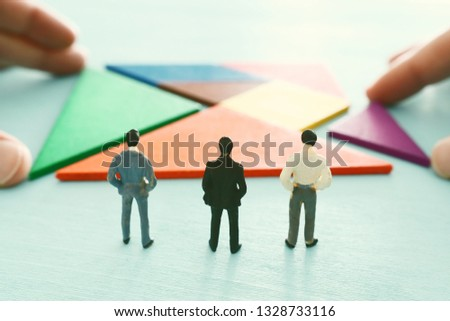 tangram puzzle blocks with miniature people over wooden table ,human resources, problem solving and management concept