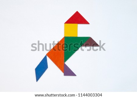 Tangram. Traditional Chinese dissection puzzle, seven tiling pieces - geometric shapes: triangles, square (rhombus), parallelogram. #1144003304