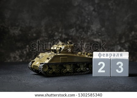 tank and calendar 23 February. February 23 Holiday background. Fatherland defender day. men's day of defenders in Russia, Belarus,Tajikistan, Kyrgyzstan. Tank toy on dark background. place for text.