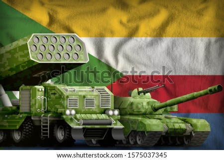 tank and missile launcher with summer pixel camouflage on the Comoros flag background. Comoros heavy military armored vehicles concept. 3d Illustration