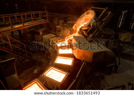 Tank pours liquid metal in the molds by carousel machine Foto stock ©