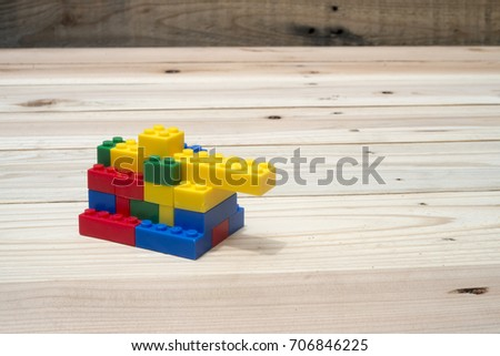 Stock Photo Tank Toy made from lego pieces on wooden background.