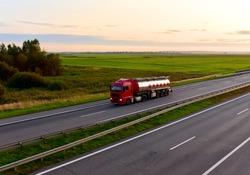 Tank transport of liquid, foodstuff. Metal chrome cistern tanker for food transportation on highway on sunset background. Soft focus