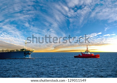 Tanker at sea towed by tug.