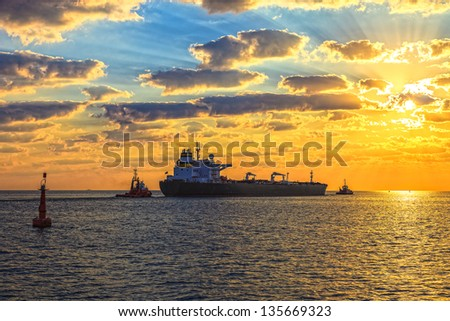Tanker at sunset putting out to sea.