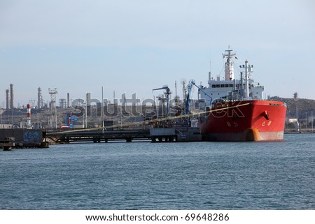 Tanker ship anchored on a dock and being loaded of gasoline