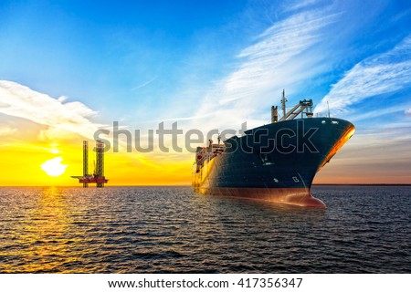 Tanker ship and Oil Platform on offshore area at sunset.