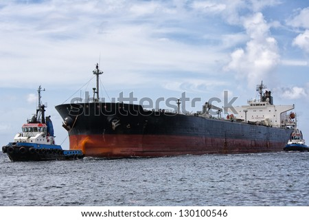 Tanker ship being pulled by tugboats