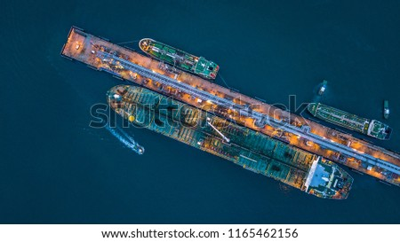 Tanker ship loading and unloading oil and gas storage at industrial port, Business import export petrol chemical oil and gas LNG tanker ship transportation, Loading arm oil and gas offshore platform.