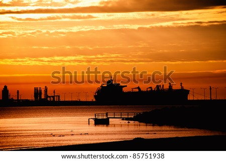Tanker ship on the background of the rising sun.