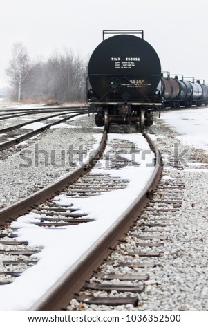 Tanker Train Cars with snow on a foggy winter day sitting on the far right set of tracks. Trees and buildings in the background. Vertical #1036352500