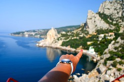 Tanned beautiful hand of a girl pointing her finger at a beautiful beach. Observation deck. Look at Simeiz from above. Crimea, travel to Russia, tourism. Selective focus.