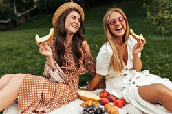 Tanned happy brunette woman in boater and beige polka dot outfit sits on white rug outside. Happy excited blonde lady in sunglasses has picnic with friend and holds piece of melon.