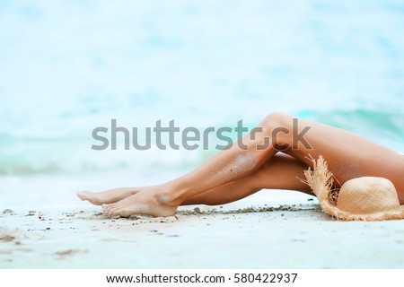 Tanned legs of a woman against the sea