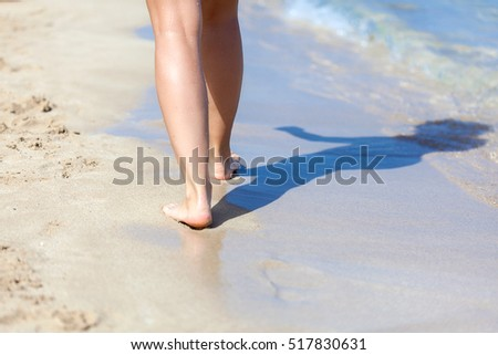 Tanned legs of sexy woman on the sandy beach #517830631