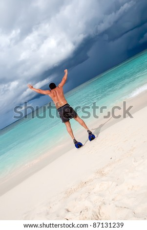 Tanned man jump in blue flippers on sand beach and ocean under gloomy sky