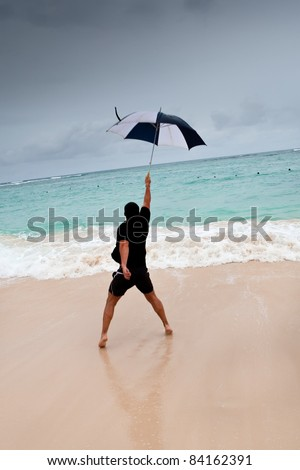 Tanned man jump with umbrella in blue sea under grey cloud sky