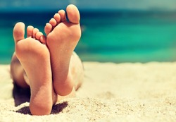Tanned well-groomed feet amid tropical turquoise sea . Pedicure and foot Spa .Care for the heels and soles of the feet .Foot massage.