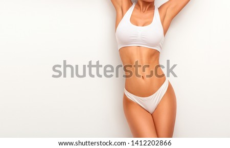Tanned woman in top form, perfect body shape. Parts of woman body  in underwear, studio shoot. #1412202866