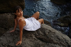 Tanned young woman in white dress sitting on a stone near the sea or lake looking back affably outgoing