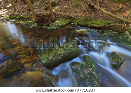 Tannin colored mountain stream and rocks in spring