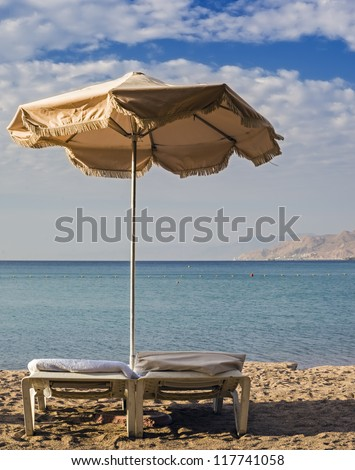 Tanning bed and sunshade on sandy beach of Eilat - popular resort and recreational city of Israel