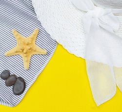 Tanning oil on a yellow background. Smooth tan. Perfect body. The beauty . Sun protection. Beach rest. Article about means for suntan. Summer vacation. Sea stones. Zen