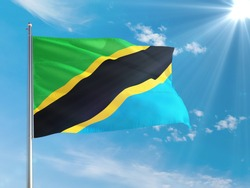 Tanzania national flag waving in the wind against deep blue sky. High quality fabric. International relations concept.