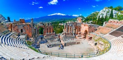 Taormina, Sicily, Italy: The Greek Theater of Taormina with smoking Etna volcano in background, in a beautiful day of summer