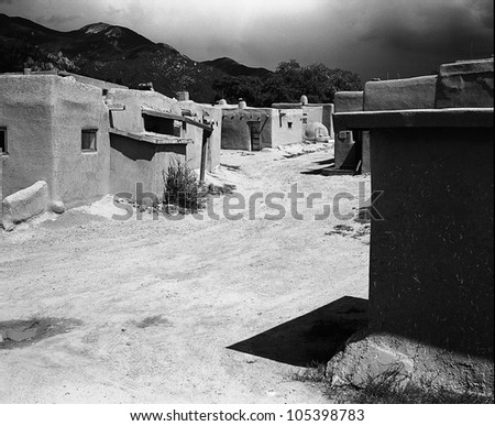 TAOS, NEW MEXICO - SEPTEMBER 7: A road meanders through adobe buildings of a native American pueblo on September 7, 2011 in Taos, New Mexico. The Taos Pueblo is a UNESCO World Heritage site.
