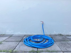 Tap on the blue wall with the long plastic hose on the cement block for gardening or wash the car, household equipment