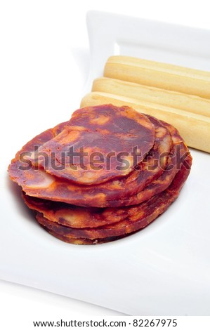 tapa of red spanish chorizo slices with bread sticks on a white background