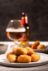 Tapas croquettes, traditional Spanish or French snack with bottle of beer on the background